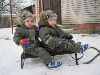 Двойня катается на деревянных санках