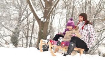 Мама и дочь катаются на деревянных санках