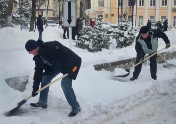 Уборка снега на улице с помощью платистиковой лопаты